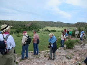 Hikers look over the edge of the buffalo jump to the valley below. The Sanson family owned this property from 1882 to 1987. It then was purchased by the Casey family. The Conservation Fund, a nonprofit dedicated to protecting important places across America, acquired the property at auction from the Casey family when it became available, and held it until federal funds became available to purchase it. The land is now part of Wind Cave National Park.
