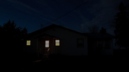 Darkness ranch house with lights on